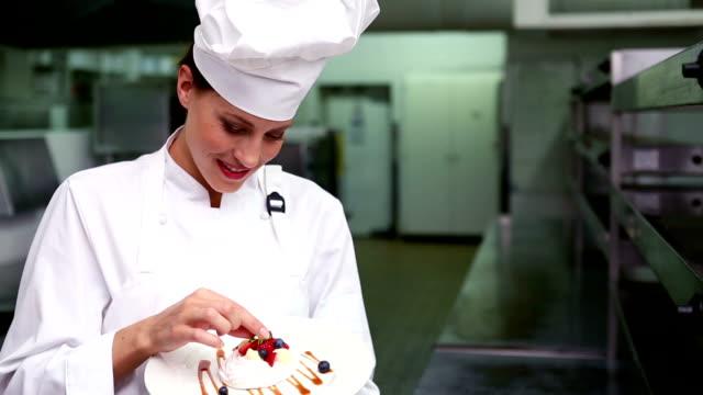 vídeos de stock, filmes e b-roll de feliz chef acompanhamentos prato de sobremesa - comida doce
