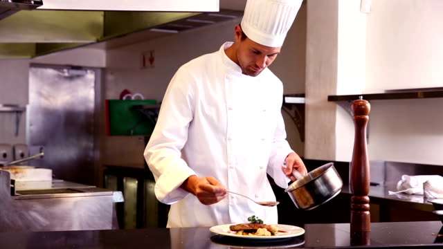happy chef pouring sauce onto beef dish - brühe stock-videos und b-roll-filmmaterial