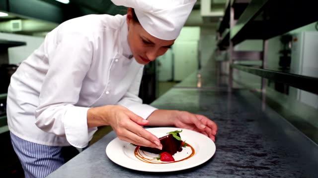vidéos et rushes de heureux chef mettre feuille de menthe sur assiette à dessert - cuisinière