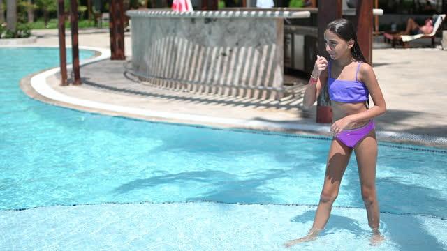 stockvideo's en b-roll-footage met happy child girl jumping to swimming pool - badkleding
