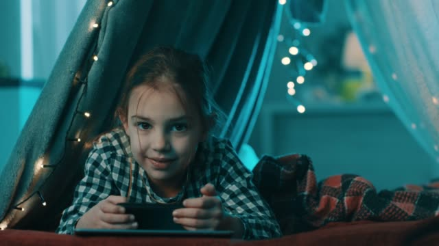 vídeos de stock e filmes b-roll de happy child girl with smartphone smiling in tent at home - criancas