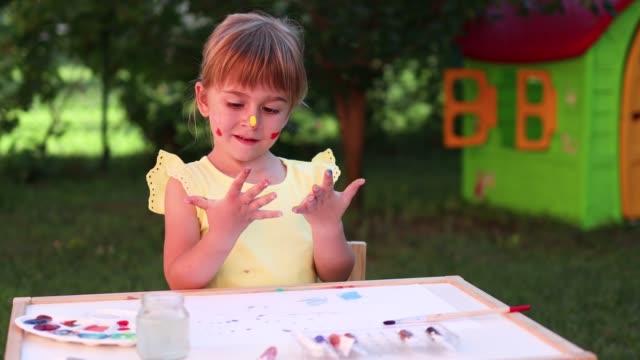 lyckligt barn med färg på hennes ansikte - endast flickor bildbanksvideor och videomaterial från bakom kulisserna