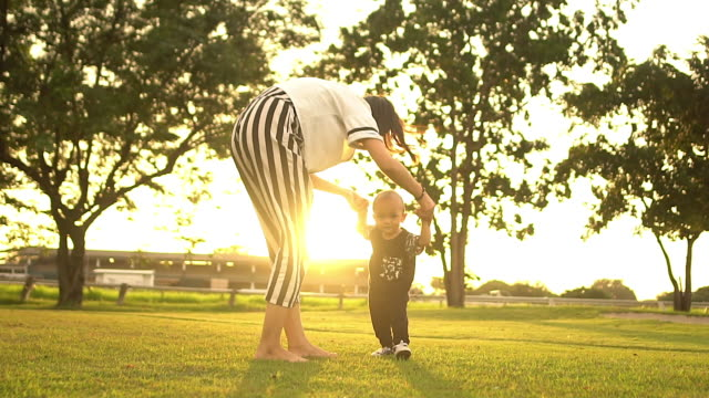 happy child making first steps in a park - sunny stock videos & royalty-free footage