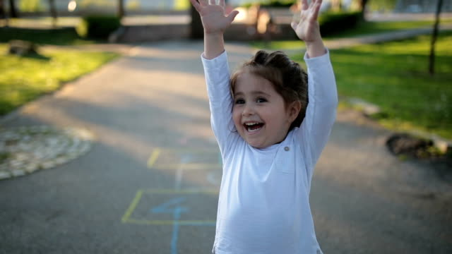 happy child on a playground playing hopscotch - arms raised stock videos & royalty-free footage