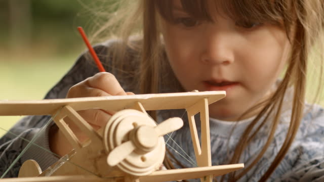 happy child painting a wooden airplane model on a beautiful summer morning at the porch. - model aeroplane stock videos & royalty-free footage