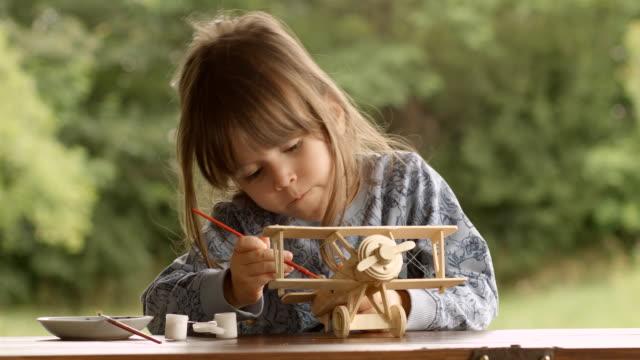 Gelukkig kind schilderen van een houten vliegtuig-Model op een mooie zomer-ochtend op de veranda.