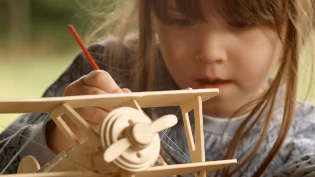 GENDER NEUTRAL KIDS. Happy Child Painting a Wooden Airplane Model on a Beautiful Summer Morning at The Porch.