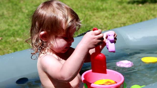 stockvideo's en b-roll-footage met gelukkig kind spelen in het zwembad - naakte meisjes