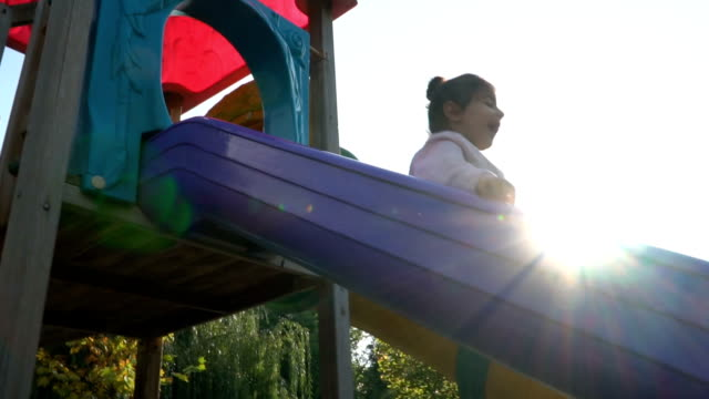happy child playing on a slide at the playground - sliding stock videos & royalty-free footage
