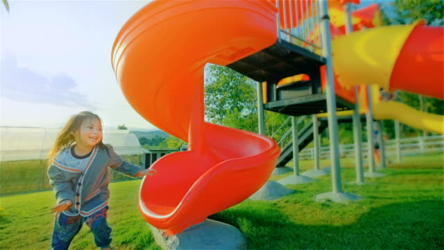 happy child playing on a slide at the playground - parco giochi video stock e b–roll