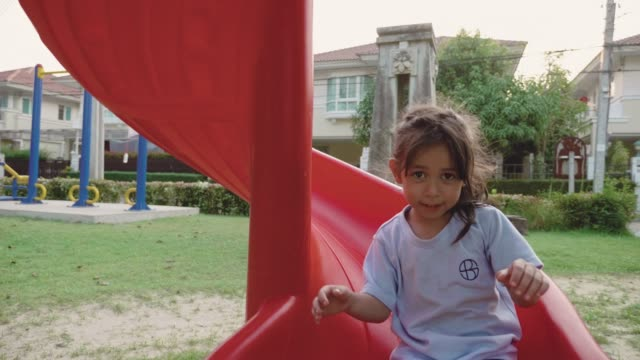 happy child playing on a slide at the playground - moving down stock videos & royalty-free footage