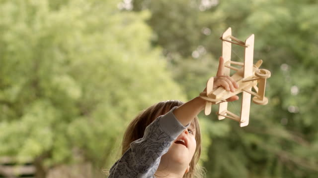 happy child playing with wooden airplane model on a beautiful summer morning at the porch - model aeroplane stock videos & royalty-free footage