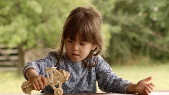 Happy Child Playing With Wooden Airplane Model on a Beautiful Summer Morning at The Porch