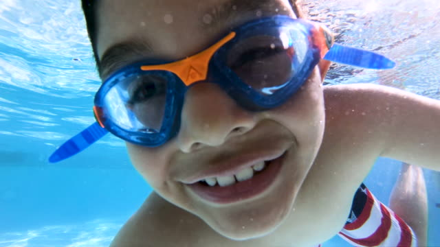 vídeos de stock e filmes b-roll de happy child posing and making signs underwater - criancas