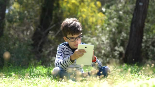 happy child using digital tablet in forest - eyewear stock videos & royalty-free footage