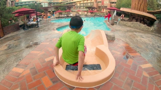 Happy Child Using Water Slide into Swimming Pool