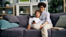 Happy child watching TV with mother at home on sofa holding remote control