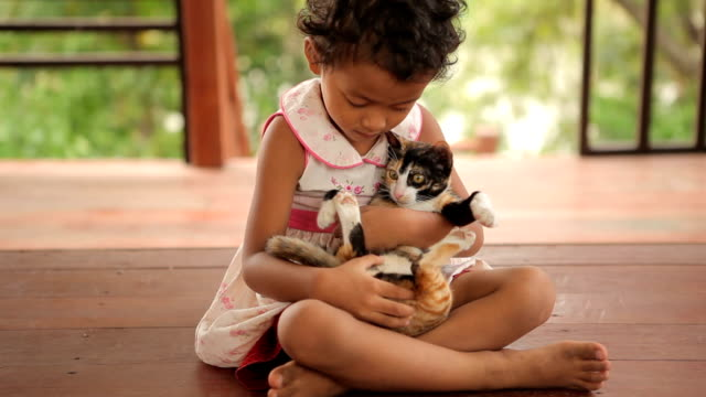 Happy child with cat in home