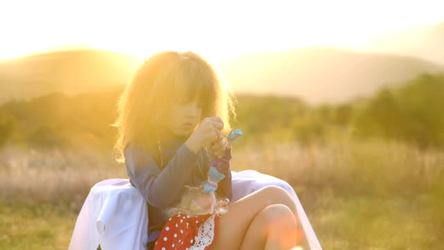 vídeos de stock e filmes b-roll de happy child with doll in sunset - vestuário
