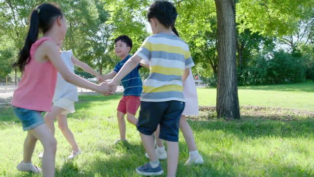 vidéos et rushes de happy children playing on meadow,4k - zoom avant
