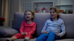 Happy children watching comedy film sitting sofa, having fun, laughing together