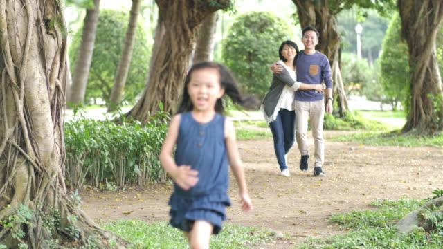 vídeos de stock, filmes e b-roll de família chinesa feliz com a filha no parque - brincadeira de pegar