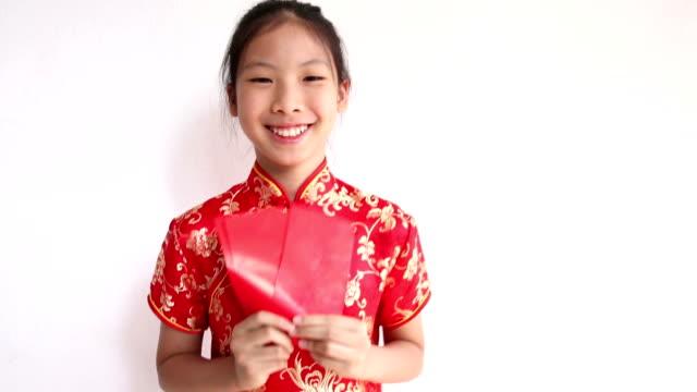 stockvideo's en b-roll-footage met happy chinese new year. smiling asian girl holding red envelope - chinees nieuwjaar