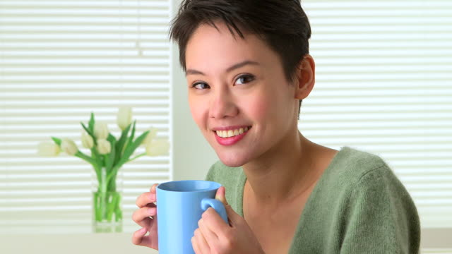 Happy Chinese woman drinking tea