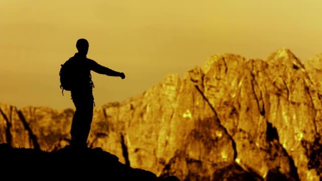vídeos de stock e filmes b-roll de hd: alpinista levantar seus braços feliz em vitória - pico da montanha