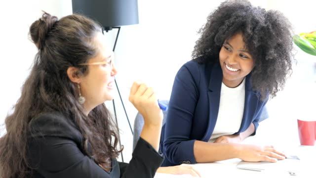 glückliche kollegen diskutieren bei inbetriebnahme büro - arbeitskollege stock-videos und b-roll-filmmaterial