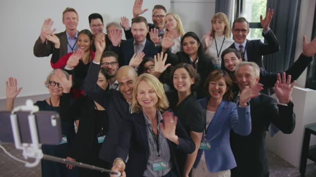 glückliche kollegen machen ein selfie mit dem handy im seminar - wissenschaft und technik stock-videos und b-roll-filmmaterial