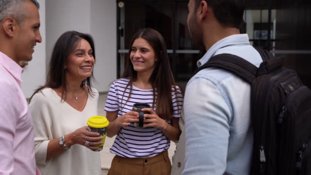オフィスビルの外に立って、話しながらコーヒーを飲みながら休憩する幸せな同僚 - 1日目点の映像素材/bロール