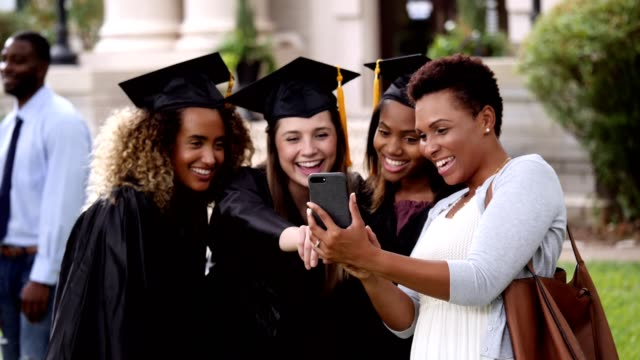 happy college friends review graduation photos - mortar board stock videos & royalty-free footage