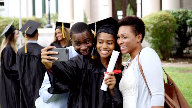 happy college grad takes selfies with parents - post secondary education stock videos & royalty-free footage