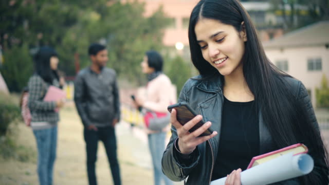 happy college student using smart phone. - indian ethnicity stock videos & royalty-free footage