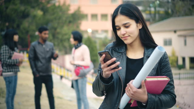 vídeos de stock e filmes b-roll de happy college student using smart phone. - povo indiano