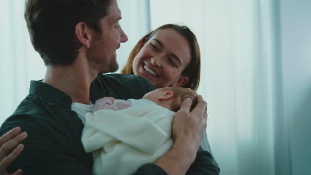 glückliches paar bewundert neugeborenes im krankenhaus - new life stock-videos und b-roll-filmmaterial
