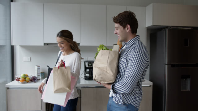 happy couple arriving home after grocery shopping talking and smiling - unpacking stock videos & royalty-free footage