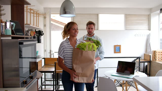 happy couple arriving home carrying their groceries and unpacking them on kitchen counter while talking and smiling - carrying stock videos & royalty-free footage