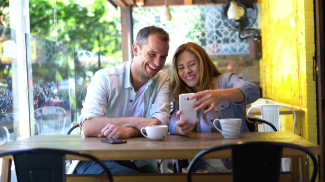 Happy couple at a cafeteria drinking coffee and looking at photos on smartphone