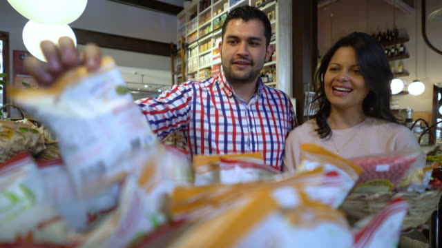 Happy couple at a gastronomy market choosing products to buy putting them in a basket