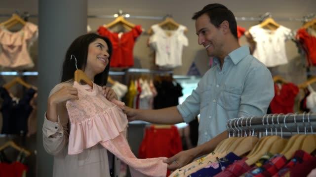 vídeos de stock, filmes e b-roll de casal feliz em uma loja olhando as roupas e caminhando em direção à câmera, enquanto mulher mostra parceiro algo que ela gostou - shopping center