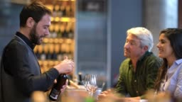 Happy couple at a wine tasting talking to the professional taster while he is opening the wine all smiling