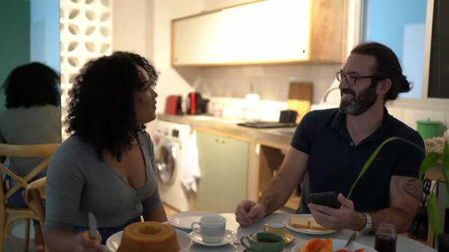 happy couple at home having breakfast together and using smartphone - breakfast stock videos & royalty-free footage