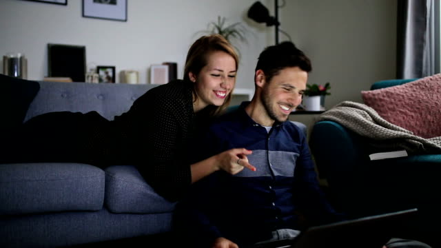 happy couple at home surfing the net on laptop - husband stock videos & royalty-free footage