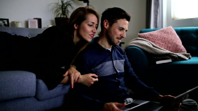 happy couple at home surfing the net on laptop - wife stock videos & royalty-free footage