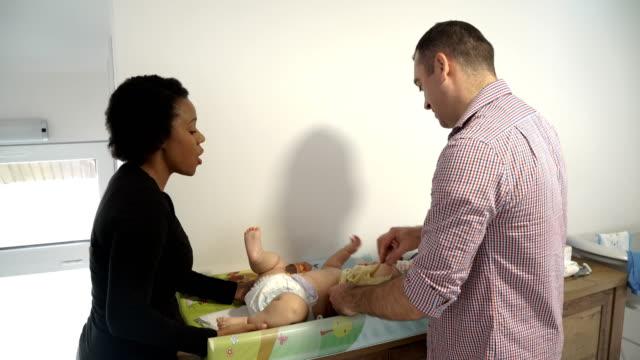 vídeos y material grabado en eventos de stock de pareja feliz cambiando pañal a su adorable niño pequeño - cambiar pañal