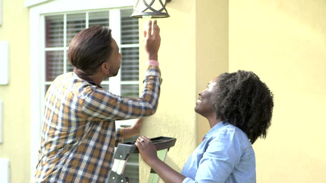 happy couple changing lightbulb outside house - changing lightbulb stock videos & royalty-free footage