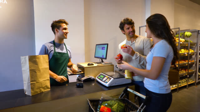 happy couple checking out of a food store and male cashier registering the products on the system and putting them in a paper bag - paper bag stock videos & royalty-free footage