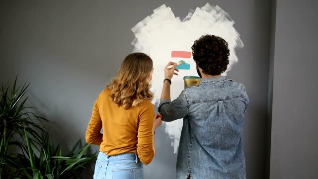 vídeos de stock e filmes b-roll de happy couple choosing colors for their living room - pano de protecção